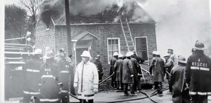 Structural Fire Training in Washington in the 1970's. Buildings donated by local residents to be burned for training purposes were not uncommon, before several thousand pages of rules were developed by the EPA. Fire Chief Don Hahne is in the foreground of the photo in the white gear and Instructor Westhoff is in the white helmet at the right corner of the structure. A great time was had by all.